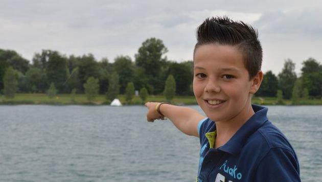 Sven Kofler (11) zeigt jene Stelle am Ausee, wo ihn ein Hecht in die Zehen gebissen hat. (Bild: LifeRadio)