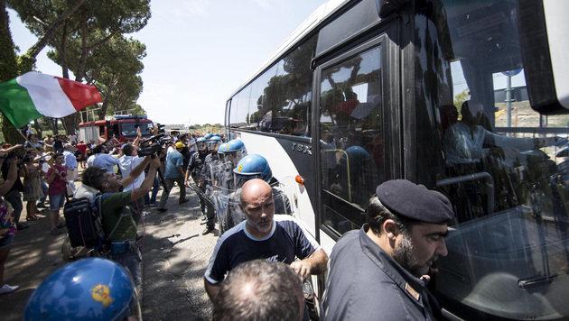 Die Polizei musste einen Sicherheitskordon um den Bus mit den Flüchtlingen bilden. (Bild: AP)