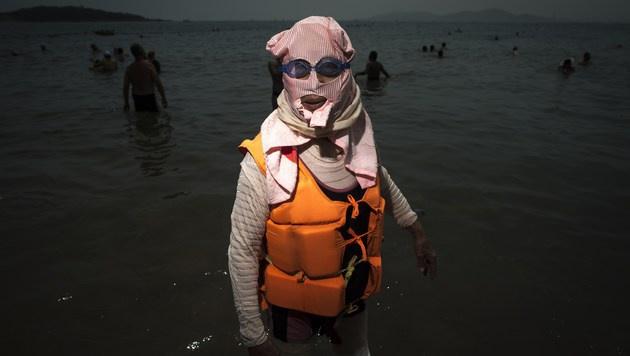"""Da kann wirklich nichts mehr passieren: """"Facekini"""", Schwimmbrille und sogar eine Schwimmweste. (Bild: AFP)"""