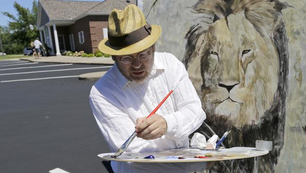 Künstler Mark Balma schloss sich den Protesten an, indem er ein Porträt von Cecil anfertige. (Bild: AP)