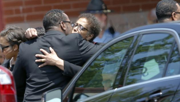Bobbi Kristinas Vater Bobby Brown mit einer trauernden Angehörigen vor der Kapelle (Bild: AP)