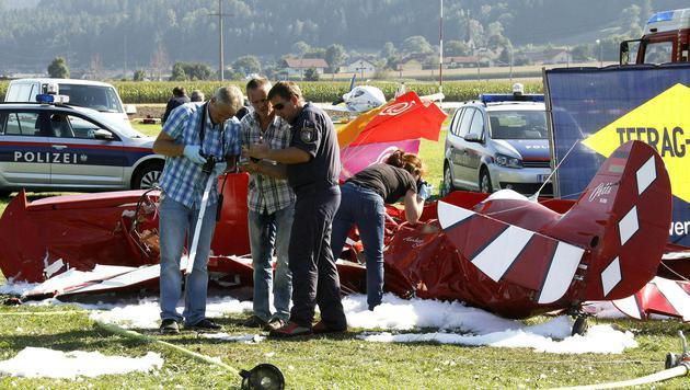 Einsatzkräfte der Polizei untersuchen das abgestürzte Flugzeug. (Bild: APA/GERT EGGENBERGER)