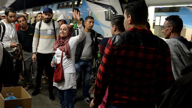 Flüchtlinge mit einer Dolmetscherin am Wiener Westbahnhof (Bild: APA/ROLAND SCHLAGER)