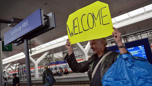 Ein Fahrgast heißt die am Salzburger Bahnhof ankommenden Flüchtlinge willkommen. (Bild: APA/EPA/BARBARA GINDL)