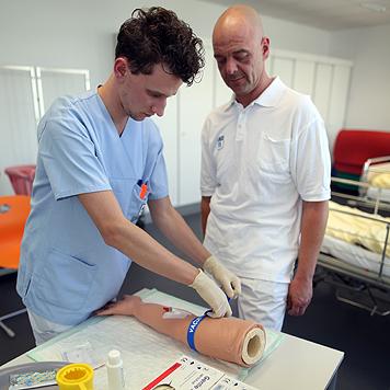 Ein Stich, der nicht wehtut: Pflegeschüler Kevin legt an einem Plastikarm eine Infusion. (Bild: Gerhard Bartel)