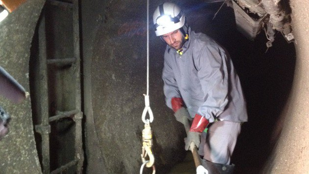 Ein Kanalarbeiter schaufelt Ablagerungen in einen Kübel. (Bild: Conny Derdak)