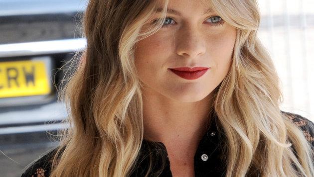 Cressida Bonus bei der London Fashion Week mit knallrotem Lippenstift und schwarzem Spitzenkleid (Bild: AP)