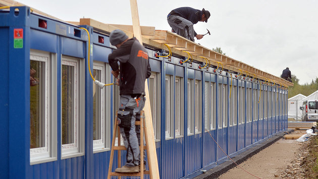 Arbeiter bei der Errichtung eines Containerdorfes in der Salzburger Schwarzenberg-Kaserne (Bild: APA/BARBARA GINDL)