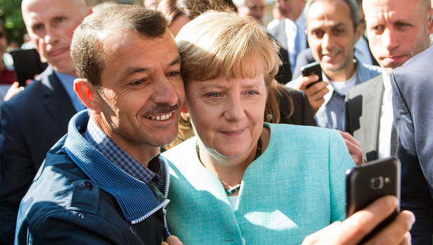 Angela Merkel mit einem Flüchtling (Bild: APA/EPA/BERND VON JUTRCZENKA)