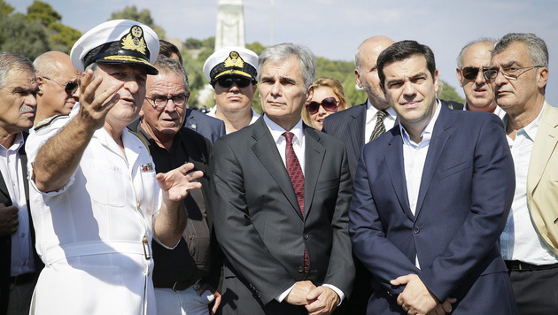 Ein Marineoffizier erklärt Faymann und Tsipras die Lage auf Lesbos. (Bild: APA/EPA/ANDY WENZEL)