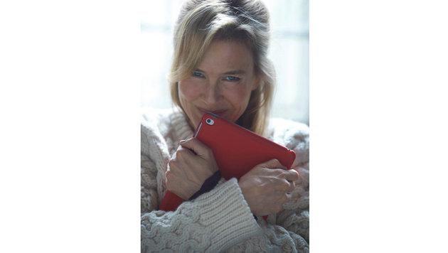 Bridget Jones lächelt in diesem ersten offiziellen Filmfoto im dicken Strickpulli hinter ihrem iPad. (Bild: Viennareport)