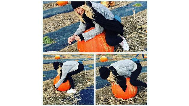 Model Nadine Leopold versucht vergebens einen Riesenkürbis nach Hause zu tragen. (Bild: Viennareport)