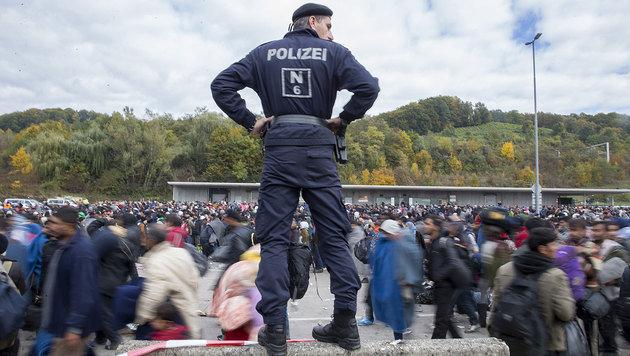Flüchtlinge überqueren die Absperrungen im Sammelzentrum an der Grenze in Spielfeld. (Bild: APA/ERWIN SCHERIAU)