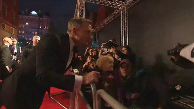 Daniel Craig schreibt schon fleißig Autogramme am roten Teppich. (Bild: YouTube.com)