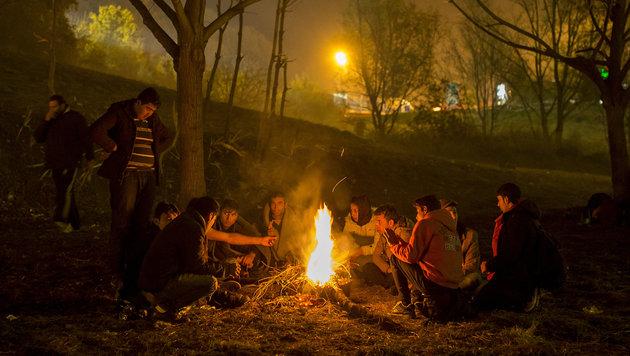 Flüchtlinge wärmen sich an der steirisch-slowenischen Grenze an einem Lagerfeuer. (Bild: APA/ERWIN SCHERIAU)
