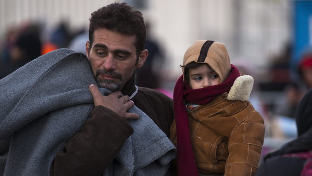 Mit seinem erschöpften Kind am Arm traf dieser Flüchtling in Spielfeld ein. (Bild: APA/EPA/ERWIN SCHERIAU)