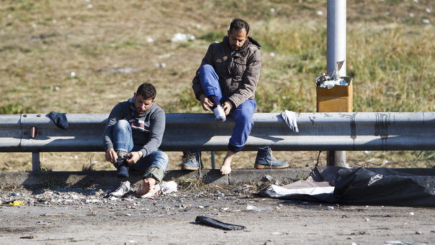 Zwei Flüchtlinge in Slowenien bereiten sich auf den Grenzübertritt nach Österreich vor. (Bild: APA/EPA/GYORGY VARGA)