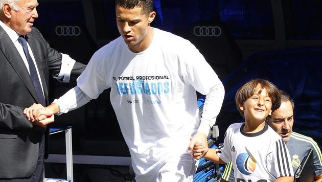 Der kleine Zaid durfte in Madrid Reals Star Cristiano Ronaldo aufs Spielfeld begleiten. (Bild: APA/EPA/ALBERTO MARTIN)