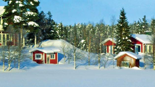 Finnland im Winter - malerisch bedeckt der Schnee Landschaft und Häuser. (Bild: Andrea Thomas)