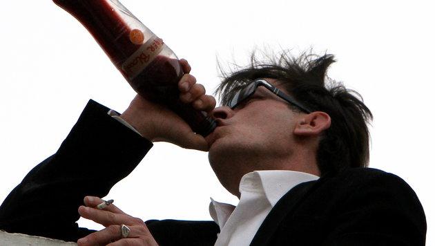 """Sheen in einer Exzess-Phase: Er kippt eine Flasche mit rotem Inhalt. """"Tigerblut"""" steht drauf. (Bild: Viennareport)"""
