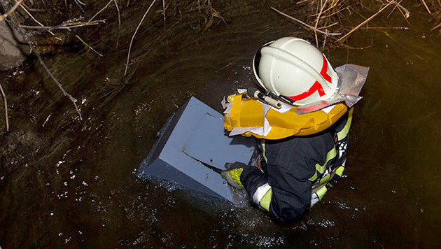 Ein Feuerwehrmann holte den Safe aus dem Bachbett. (Bild: APA/BFK BADEN/STEFAN SCHNEIDER)