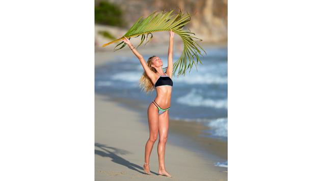 Candice Swanepoel wirft sich mit einem Palmwedel in sexy Pose. (Bild: Viennareport)
