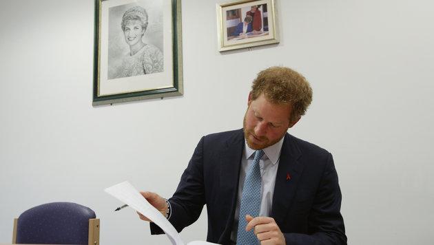 Wie seine Mutter Diana (Foto oben an der Wand) trägt Prinz Harry sich ins Gästebuch ein. (Bild: AP)