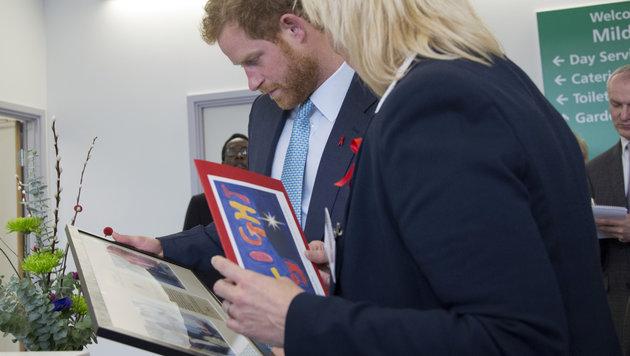 Prinz Harry betrachtet Fotos seiner Mutter Diana beim Besuch in der Klinik. (Bild: AP)