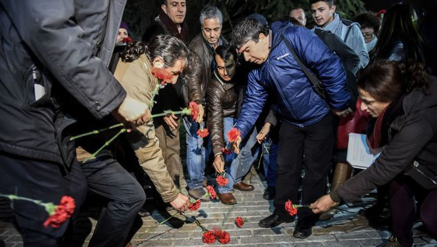 Menschen legen Blumen am Ort des Anschlag nieder. (Bild: APA/AFP/OZAN KOSE)