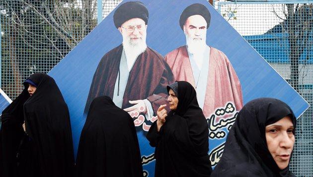 """Frauen vor einem Bild von """"Perser-Papst"""" Ali Khamenei und dessen Vorgänger Ayatollah Khomeini (Bild: EPA)"""