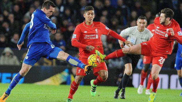 Christian Fuchs (ga. li.) nimmt es gleich mit zwei Liverpool-Kickern auf. (Bild: AP)