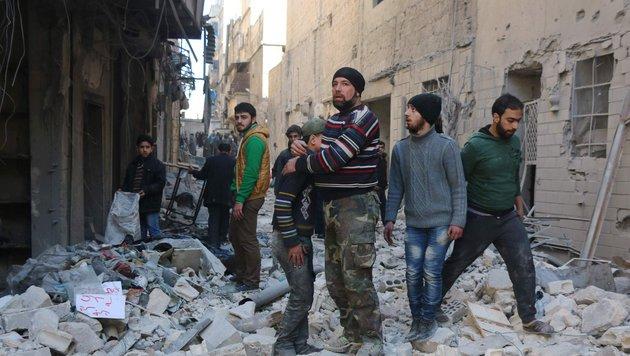 Ein Einwohner von Aleppo tröstet einen Buben inmitten der Trümmer. (Bild: APA/AFP/THAER MOHAMMED)
