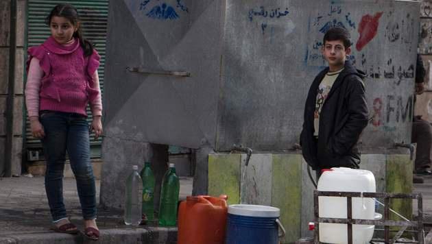 Syrische Kinder füllen Wassercontainer. Die humanitäre Lage im Land ist angespannt. (Bild: APA/AFP/KARAM AL-MASRI)