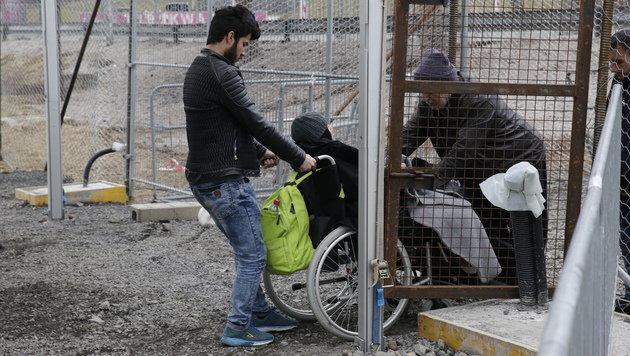 Ein junger Mann bringt seine Mutter im Rollstuhl �ber die Grenze. (Bild: Klemens Groh)