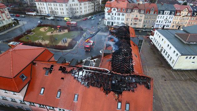 Schaulustige bejubeln Brand einer Asylunterkunft (Bild: APA/dpa/Christian Essler)