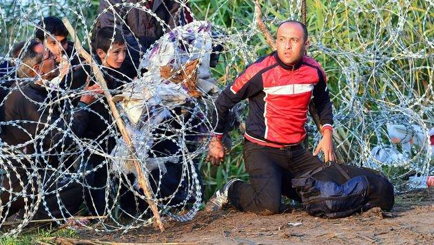 Flüchtlinge überwinden im Spätsommer 2015 eine ungarische Grenzsperre. (Bild: AFP)