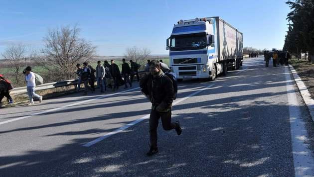 Flüchtlinge versuchen, über die Autobahn nach Mazedonien zu gelangen. (Bild: APA/AFP/SAKIS MITROLIDIS)