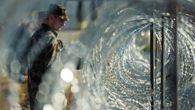 Slowenische Soldaten kontrollieren eine Grenzsperre. (Bild: APA/AFP/Jure Makovec)