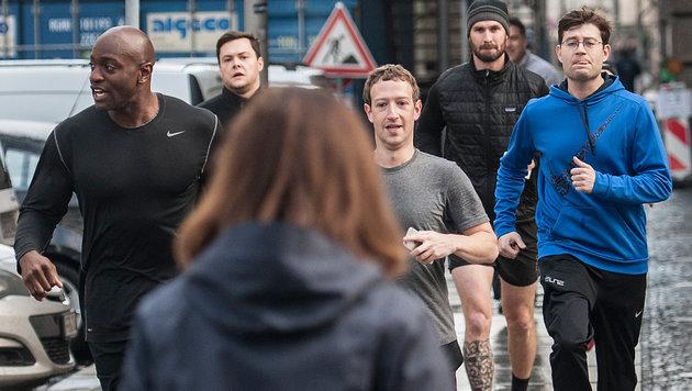 Mark Zuckerberg mit seiner Entourage - in der Hand hält er ein Handy. (Bild: Paul Zinken / dpa / picturedesk.com)