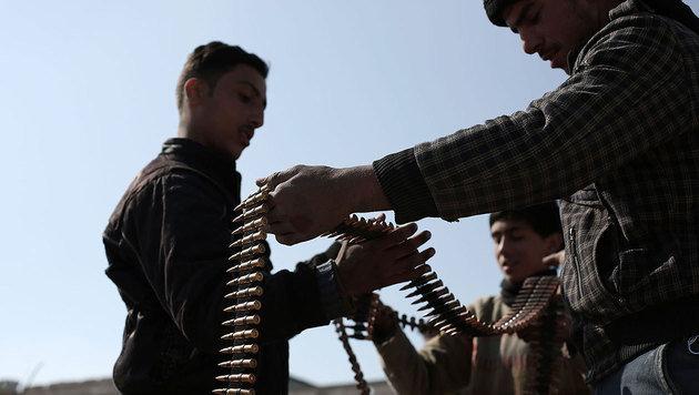 Syrische Rebellen bei der Überprüfung eines Munitionsgurtes (Bild: APA/AFP/AMER ALMOHIBANY)