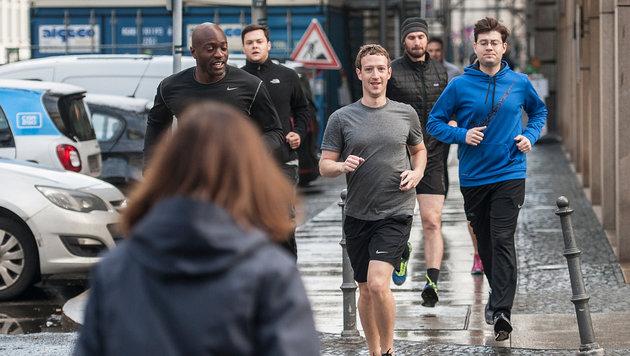 Mark Zuckerberg lächelt beim Laufen einer entgegenkommenden Frau zu. (Bild: Paul Zinken/dpa/picturedesk.com)