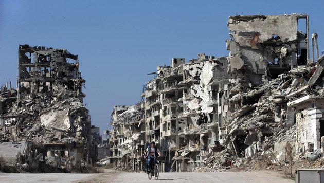 Ein Bub radelt durch die völlig zerstörte Stadt Homs. (Bild: AP)