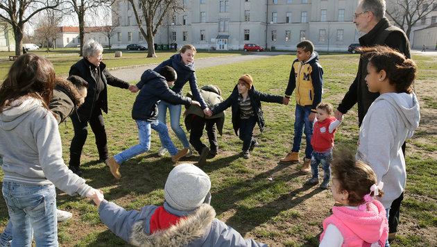 Am Traiskirchen-Areal: Auf der Wiese spielen Kinder, nur wenige Männer lungern herum. (Bild: Klemens Groh)