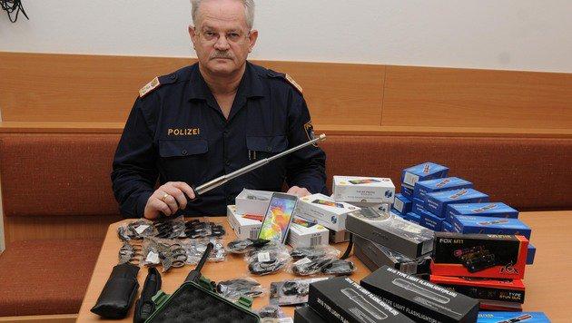 Ermittler Christian Lackstätter von der Polizei Kufstein mit den sichergestellten illegalen Waffen. (Bild: ZOOM-TIROL)
