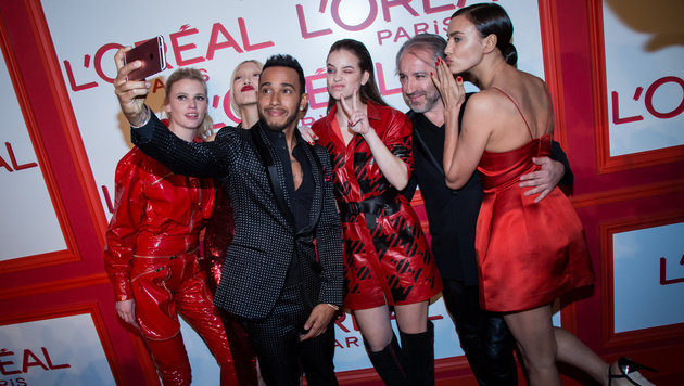 """""""Lebemann"""" Lewis Hamilton mit Models bei einer Werbeveranstaltung (Bild: AP)"""