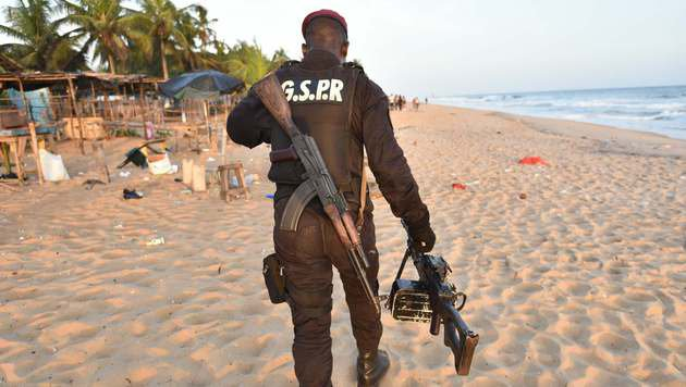 Ein schwer bewaffneter ivorischer Soldat am Strand, wo zahlreiche Menschen den Tod fanden (Bild: APA/AFP/SIA-KAMBOU)