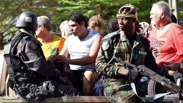 Touristen werden von Soldaten in Sicherheit gebracht. (Bild: APA/AFP/SIA-KAMBOU)