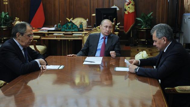 Putin mit Außenminister Sergej Lawrow (li) und Verteidigungsminister Sergej Schoigu (re) (Bild: AP)