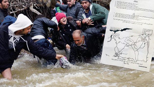 """Flüchtlinge im Hochwasser führenden Grenzfluss, Flugblatt mit Wegbeschreibung (Bild: AFP PHOTO / DANIEL MIHAILESCU, """"Krone"""")"""