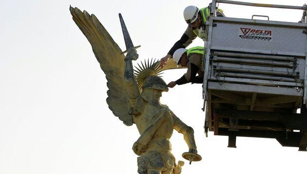 Nach der Landung wurden Teile des Helms wieder am Erzengel befestigt. (Bild: APA/AFP/CHARLY TRIBALLEAU)